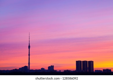 early pink sunrise colors under city with tv tower