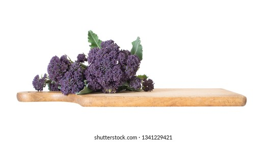 Early purple sprouting broccoli spring vegetable, with wooden food cutting board. Isolated on white. Low angle view.