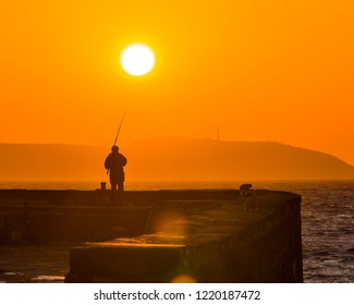 An early rising fisherman is bathed in the beautlful Autumnal sun as he patiently waits for a bite in Charlestown, Cornwall.