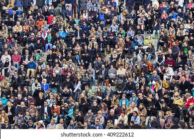 Early spring afternoon at the Mauerpark amphitheater. Crowd of people sitting on the stone terraces watch as a funny performance on easter sunday. Berlin, Germany 27th March 2016