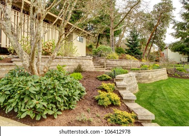 Early Spring Landscape with retaining walls and garage on the back.