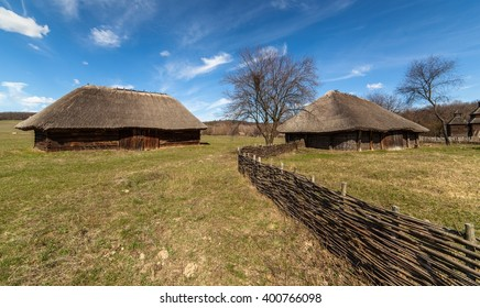 Early spring. Rural landscape with wooden sheds and wicker fence.