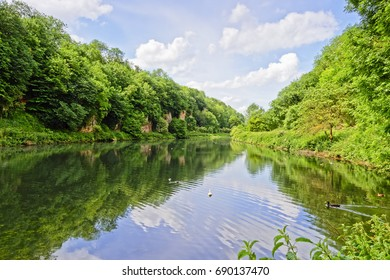 Early summer morning sky reflected in the still water of a tree lined lake at Creswell Crags in derbyshire
