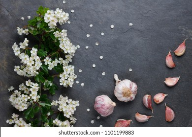 Early summer white  flower blossoms with pink garlic on slate with copy space