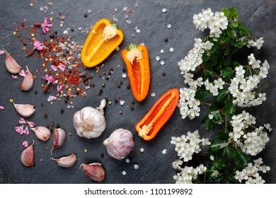 Early summer white  flower blossoms with pink garlic and Himalayan pink rock salt with colorful pepper and chili on slate