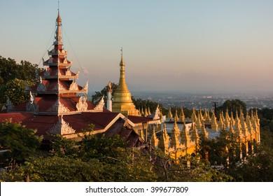 Early sunset view from Mandalay hill at Su Taung Pyai Pagoda  down to the city over illuminated Chedis