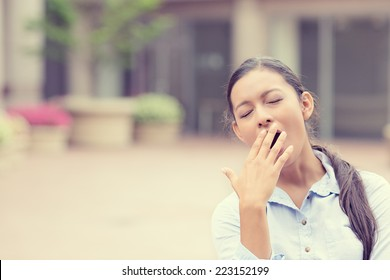 It is too early for this meeting. Portrait sleepy young business woman covering with hand wide open mouth yawning eyes closed looking bored isolated outside office background. Emotion face expression