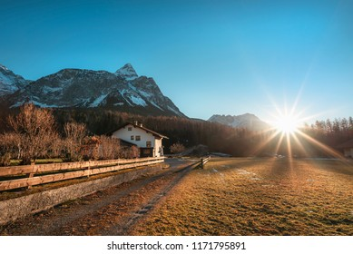 Early winter landscape with dried grass, leafless trees, the Austrian Alps mountains and a bright sun with its rays, in Ehrwald, Austria.