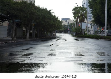 Early winter morning in Tel-Aviv, the wet street is empty from vehicles and people.