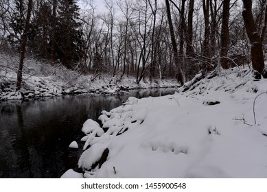 An early winter snow fall when the river waters are still open with the various leafless trees reflecting in the dark waters of the Pike River.