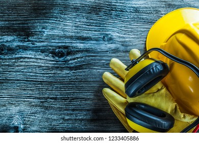 Earmuffs safety gloves cap on wooden board.
