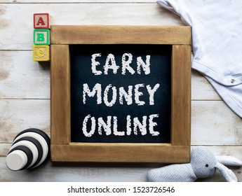 Earn money online written on a blackboard surrounded by baby toys and clothes - stay at home mum money  concept