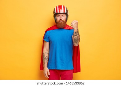 Earnest bearded man clenches fists, shows strength, ready to revenge evil for bad things, wears cartoon costume, pretends being superhero, has power in his hands, isolated on yellow background