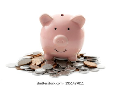 Earning interest on savings, growing your wealth and saving money concept theme with a pink ceramic piggy bank sitting on top of a pile of coins isolated on white background