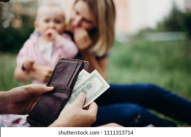 Earning money for family. Male hand with wallet and US dollar bills at family blurred background. Financial support, business, family, alimony, maintenance, investing in children concept