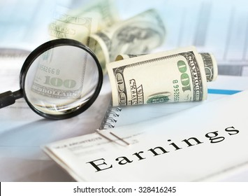 "Earnings concept. Image of selective focus shot of magnifying glass, hundred dollar bills and ""earnings"" written on pay checks."