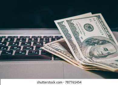 earnings on the Internet, cash lie near the computer, close-up