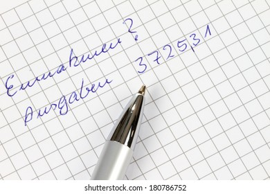 Earnings and outgoings are written in german on a checked paper decorated with a pen.