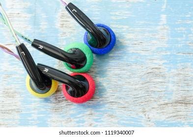 earphone stereo with Sponge earphone on wood background.
