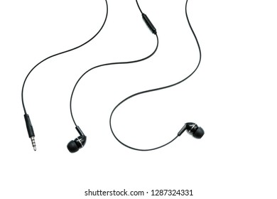 Earphones headset. In-ear headphones. Vacuum wired black headphones for listening to music and sound on portable devices on a white background. Ear plugs for music lovers.