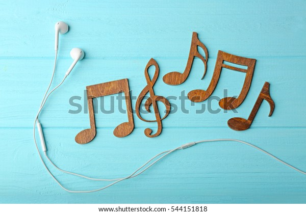 Earphones and music notes on color wooden background