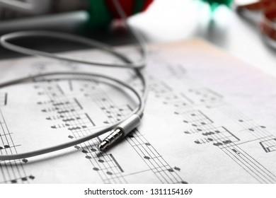 Earphones on music sheet, closeup