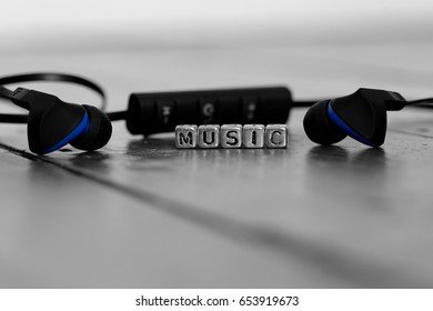 Earphones on a wooden floor with the word music on beads