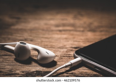 earphones and phone media portable on dark tone. selective focus of earphones.