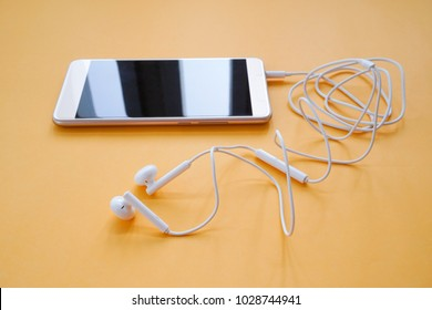 Earphones Plugs into Smartphone on Orange Background