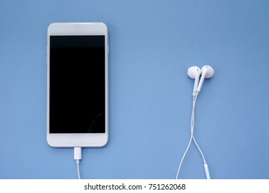 Earphones Plugs Into Smartphone on Blue Background Top View