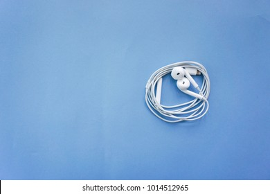 Earphones or Smalltalk for Smartphone on Blue Background Top View