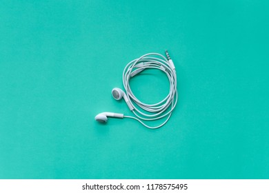 Earphones for Smartphone with 3.5mm Jack on Turquoise Background Top View