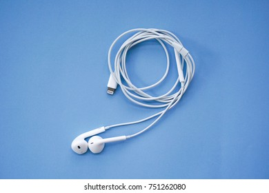 Earphones for Smartphone on Blue Background Top View