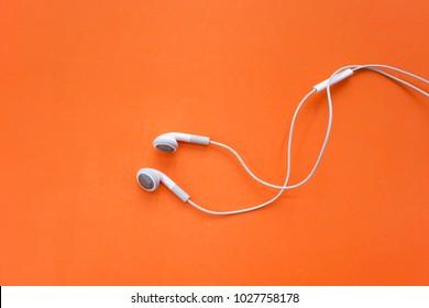 Earphones for Smartphone on Orange Background Top View