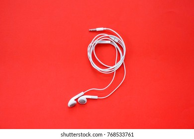 Earphones for Smartphone on Red Background Top View
