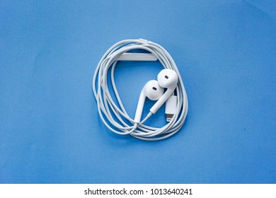 Earphones for Smartphone with Spiral Cable on Blue Background Top View