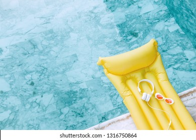 Earphones and sunglasses on yellow pool float in blue water, high view from above.