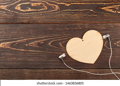 Earphones, wooden heart and copy space. Plywood heart and earphone on brown wooden background. Listen music with heart.