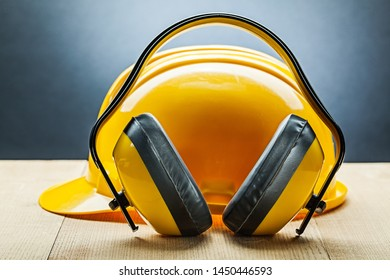 earphones with yellow construction helmet