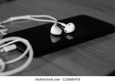Earphones/headphones on smartphone, sad music for broken heart people, black and white