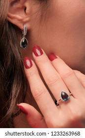 Earring in the ear and the ring on the girl's finger. Woman jeweler. Buying and shopping. Promotional photograph of jewelry.