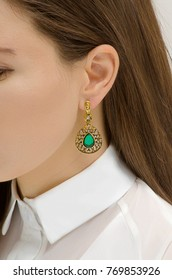 earring with emerald on the woman's ear