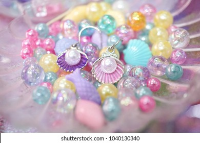 earrings. A beautiful pair of mermaid seashell earrings with pearl among the colorful beads. Mermaid fashion and fantasy concept. Soft focus.