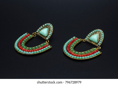 earrings in Boho style with mint and coral beads isolated on black