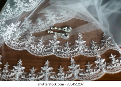 Earrings for brides with white lace, fashion accessories, wedding decorations on a brown background