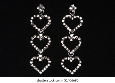 earrings in the form of hearts with precious stones on a black background