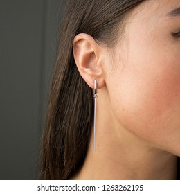earrings with a girl on the ears, a girl with beautiful dark hair, gold jewelry