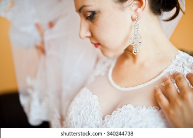 earrings on beautiful young brunette bride