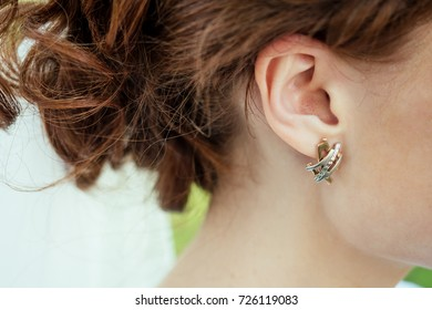 Earrings with rhinestones in the bride's ear with a beautiful hairdo