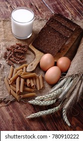 Ears of cereals, pasta, bread, eggs and milk free gmo on an old wooden table. Healthy food background.